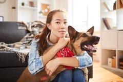 Asiatin, die mit Hund aufwirft lizenzfreie stockbilder