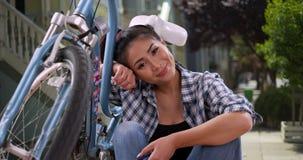 Asiatin, die mit ihrem Fahrrad lächelt lizenzfreies stockfoto