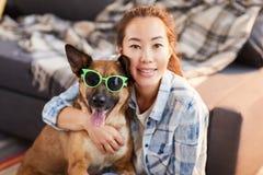 Asiatin, die mit lustigem Hund aufwirft lizenzfreie stockbilder