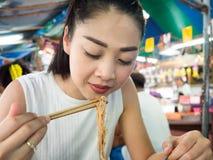 Asiatin, die Nudel im thailändischen lokalen Restaurant isst Lizenzfreies Stockbild