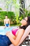 Asiatin, die am Pool sich bräunt Lizenzfreie Stockfotos