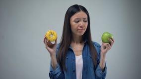 Asiatin, die süßen schmierigen Donut und saftigen grünen Apfel in den Händen, Entscheidung hält stock footage