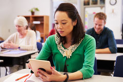 Asiatin, die Tablet-Computer in der Erwachsenenbildungsklasse verwendet stockbild