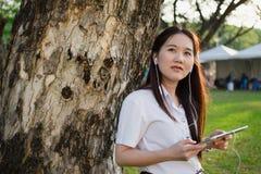 Asiatin, die Tablette verwendet und Musik hört Stockfotografie