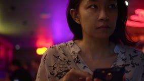 Asiatin, die Telefon an der Nachtneonbar verwendet