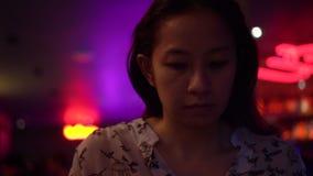 Asiatin, die Telefon ignor Leute an der Nachtneonbar verwendet