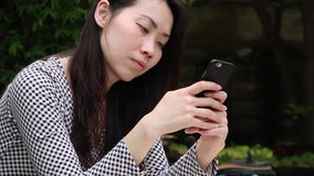 Asiatin, die am Telefon im Garten plaudert stock video footage