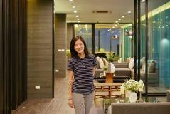 Asiatin, die vor Luxuswohnzimmer im modernen apa lächelt stockfotos