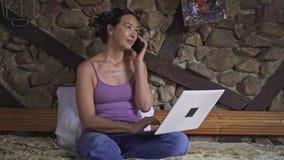 Asiatin, die zu Hause auf Laptop schreibt und auf Smartphone spricht stock video