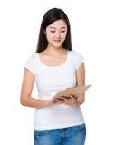 Asiatin gelesen auf Klemmbrett lizenzfreie stockbilder