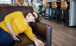 Asiatin halten auf Sofa am Café ein Schläfchen stockbild