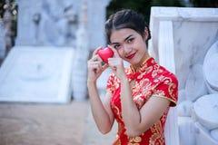 Asiatin im chinesischen Kleid traditionell mit der Geste des Glückwunsches rotes Herz halten stockfoto