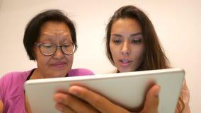 Asiatin im Ruhestand mit der jungen Mischrassetochter, die Tablettengerät verwendet 4K stock video