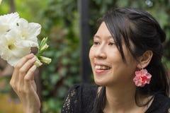 Asiatin im schwarzen Kleid, das zur weißen Blume im belaubten grünen Garten hält und schaut Stockbild