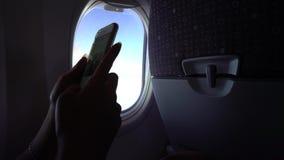 Asiatin 4k, die den Smartphone mit den Händen während des Fluges hält stock video