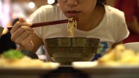Asiatin 4K unter Verwendung der Stöcke für das Essen der Rindfleischnudel, chinesische Nahrung des Restaurants stock video footage