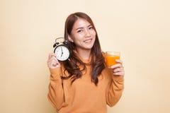 Asiatin mit einem Orangensaft des Uhrgetränks stockbilder