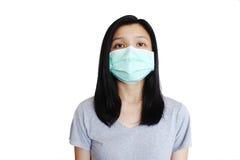 Asiatin mit Gesichtsmaske auf Reinweißhintergrund stockfotografie