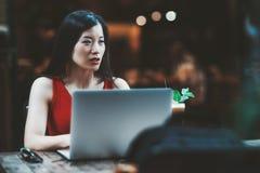 Asiatin mit Laptop in einer Stange lizenzfreie stockfotografie