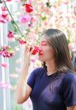 Asiatin mit rosafarbener Blume und Einfassungen das Blühen stockfoto