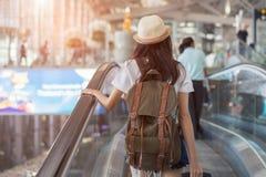 Asiatin mit Rucksack im Flughafenabfertigungsgebäude lizenzfreie stockbilder