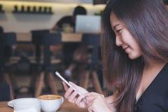 Asiatin mit smileygesicht mit und intelligentem Telefon betrachtend im modernen Café mit Kaffeetassen auf Holztisch Stockfoto