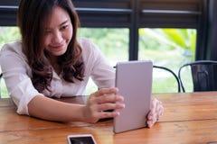 Asiatin mit smileygesichtsholding und -anwendung von Tabletten-PC im modernen Café mit grünem Naturhintergrund Stockbild
