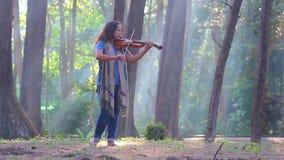 Asiatin mit Violine im Kiefernwald auf Sonnenlichtmorgen stock video
