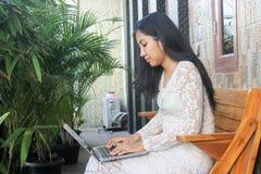 Asiatin oder Mädchen, das Laptop im Garten verwendet stockfotos