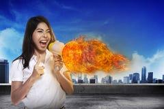 Asiatin-schreiendes Megaphon auf Feuer Stockfoto