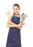 Asiatin-tragendes Schutzblech und Darstellen, Werkzeuge kochend Lizenzfreie Stockfotografie