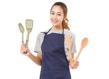 Asiatin-tragendes Schutzblech und Darstellen, Werkzeuge kochend Stockfoto