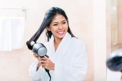 Asiatin in trocknendem Haar des Badezimmers Stockfoto