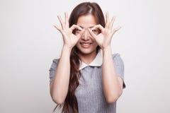 Asiatin tun lustiges doppeltes OKAYzeichen als Gläser lizenzfreies stockfoto