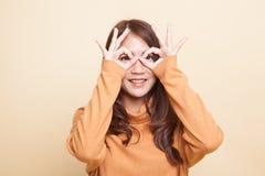 Asiatin tun lustiges doppeltes OKAYzeichen als Gläser lizenzfreies stockbild