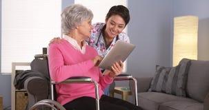 Asiatin und älterer Patient, die mit Tablette sprechen Stockfotografie