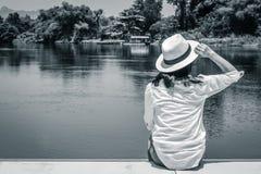 Asiatinabnutzungs-Webarthut und weißes Hemd, die auf hölzerner Terrasse sitzen und vorwärts zum Fluss schauen lizenzfreie stockfotos