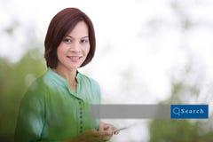 Asiatindoppelbelichtung mit grünem Hintergrund mit dem Suchen Lizenzfreies Stockfoto