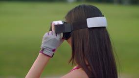 Asiatingebrauch vr Kopfhörer im Park VR-Gläser auf Frauenkopf draußen stock footage