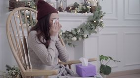 Asiatingefühlkopfschmerzen eingewickelt im grauen umfassenden Schlag die Nase und das Gebrauchsgewebe beim Lügen auf Stuhl, wenn  stock video footage