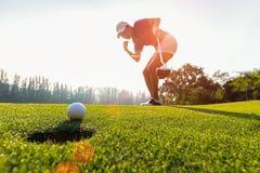 Asiatingolfspieleraktion, zum nach langem setzendem Golfball auf dem grünen Golf, Sonnenuntergangzeit zu gewinnen, stockbilder
