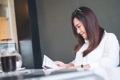 Asiatinlesebücher im weißen modernen Café mit grünem Naturhintergrund Lizenzfreie Stockfotos