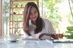 Asiatinlesebücher im weißen modernen Café mit grünem Naturhintergrund Stockbild