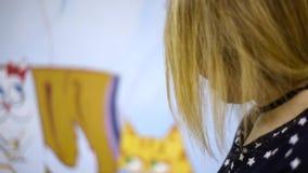 Asiatinmädchen, das mit der Katze, Kamera betrachtend spielt Erregt eine Katze stock video