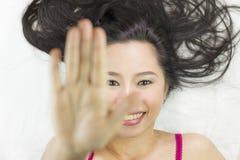 Asiatinnen, die auf dem Boden mit dem schwarzen langen Haar liegen verantwortliches Lächeln, glücklich und Endgeste zeigend stockbilder
