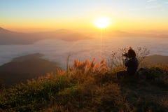 Asiatinnen, die morgens das Foto des Sonnenscheins mit vielem Nebel machen Stockbild