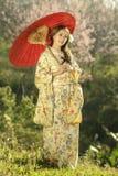 Asiatinnen, die traditionellen japanischen Kimono und roten Regenschirm tragen Lizenzfreie Stockfotos