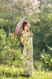 Asiatinnen, die traditionellen japanischen Kimono und roten Regenschirm tragen Stockfotos