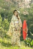 Asiatinnen, die traditionellen japanischen Kimono und roten Regenschirm tragen Lizenzfreie Stockfotografie