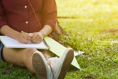 Asiatinnen, die unter dem Baum mit leerem Notizbuch sitzen Stockbild